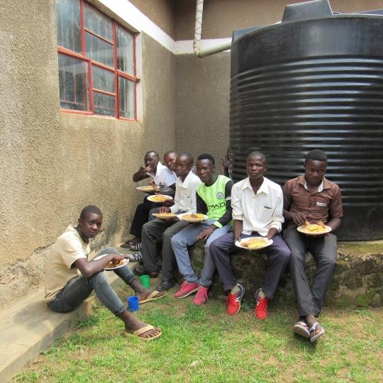 Boys eating next to water tank